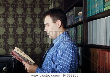 Serious Young Man In Blue Reads Book Near Shelves With Many Books