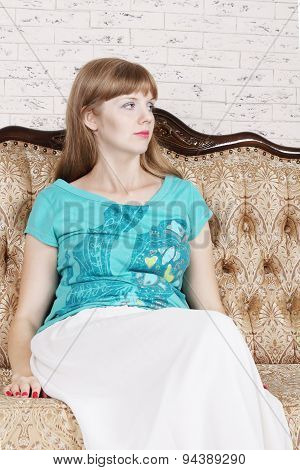 Beautiful Young Woman Sits On Couch And Looks Away In White Room