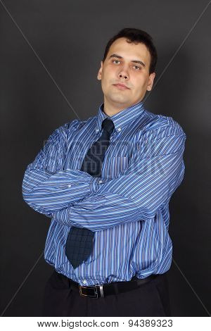 Handsome Young Cross-armed Man In Tie And Blue Shirt Stands In Black Studio
