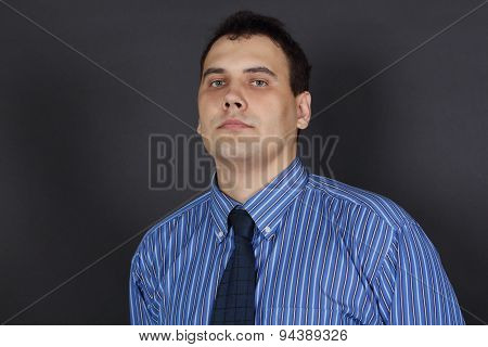 Handsome Young Serious Man In Tie And Blue Shirt Stands In Black Studio