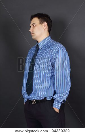 Handsome Young Man In Tie And Blue Shirt Stands In Black Studio And Looks Away