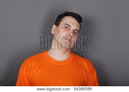 Handsome Young Man Orange T-shirt In Grey Studio Looks At Camera