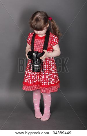 Funny Little Girl In Red Dress Holds Modern Camera In Grey Studio