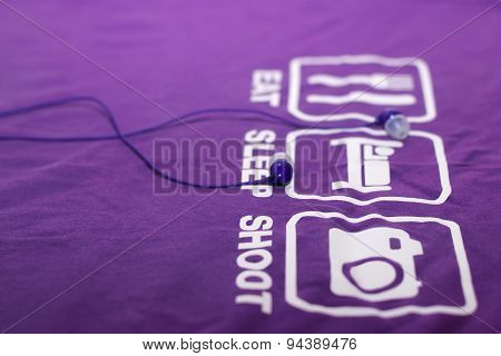 Vacuum Blue Headphones Lying On Purple T-shirt With Text Eat, Sleep, Shoot