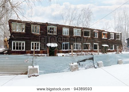 Two-storey Abandoned Wooden House Made Of Logs During Snowfall On Winter Day