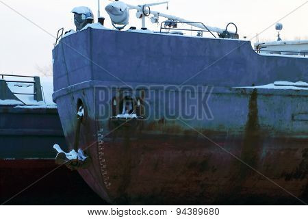 Closeup Of Blue And Rusty Prow Of Ship With An Anchor On Winter Day