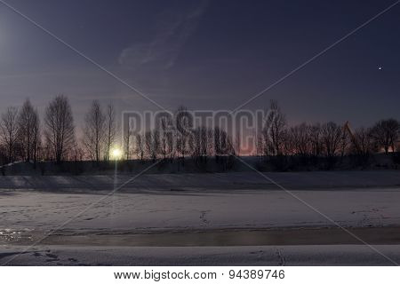 Frozen River Covered With Snow At Night And Beautiful Sky With Red Horizon