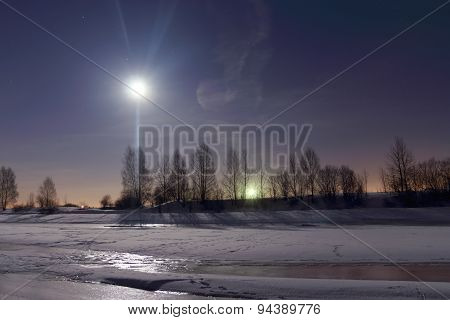 Frozen River Covered With Snow At Night And Beautiful Sky With Moon And Red Horizon Of City Lights