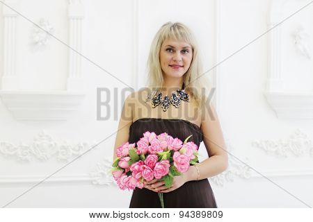 Beautiful Woman In Brown Dress Holds Pink Flowers And Sniffs It In White Studio