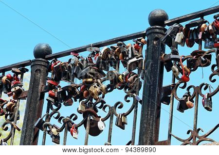 Black Forged Railings With Many Wedding Locks At Background Of Blue Sky