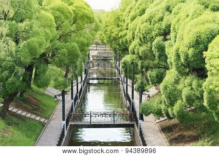 Summer Sunny Park With Green Trees, Channel, Forged Bridges And Lanterns