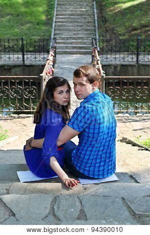 Man And Woman In Blue Sit On Stairs And Look At Camera In Park At Summer Day