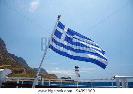 Flag of Greece on a cruise ship against greek coastline
