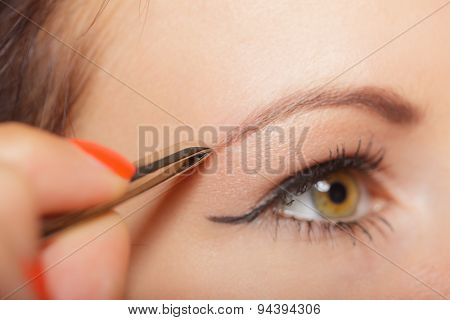 Girl Tweezing Eyebrows Closeup