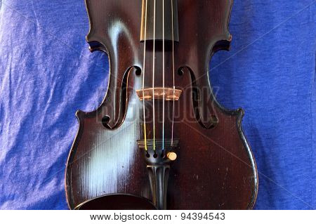 Antique Violin Against Blue Linen Backdrop