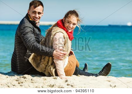 Couple Sitting On Beach Relaxing