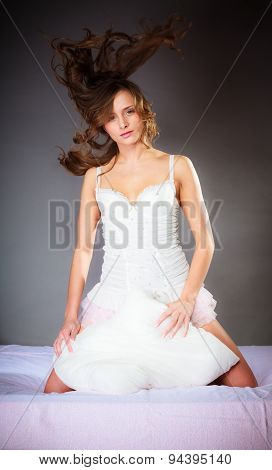 Woman On Bed With Pillow And Wind In Hair.