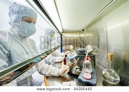 female science researchers in protective uniform and equipment works with dangerous hazard virus material at microbiology laboratory