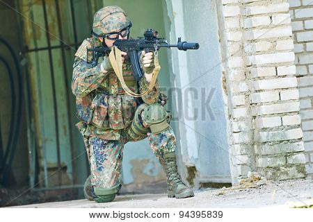 military. soldier targeting  with assault rifle at position in uniform indoors
