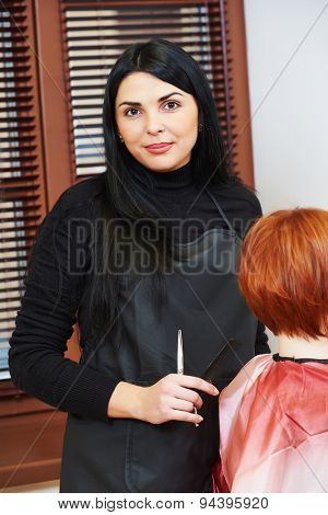 Stylist portrait during cutting hair of a female client at the beauty salon