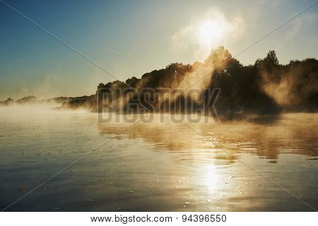 picturesque reflective landscape of foggy misty sunrise over river in summer