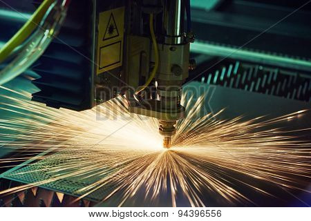 metal working. Laser cutting technology of flat sheet metal steel material processing with sparks. Authentic shooting in challenging conditions. Maybe little blurred.