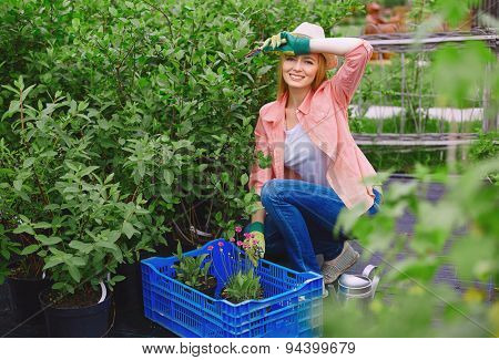 Pretty farmer looking at camera while replanting flowers