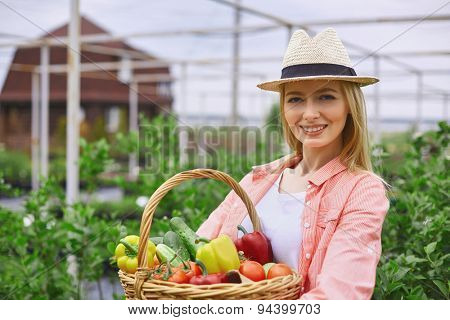 Pretty farmer with basket of fresh vegs looking at camera