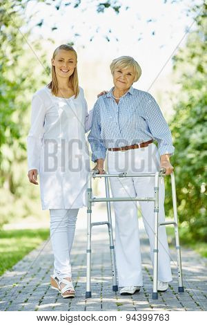 Smiling nurse and her aged patient with walking frame looking at camera outside