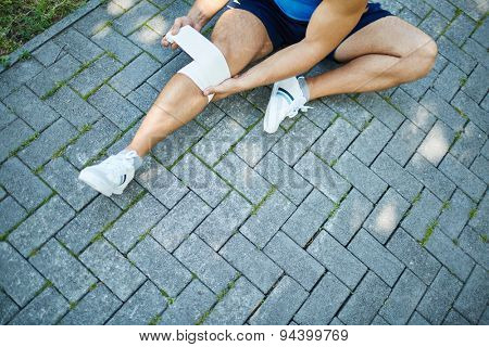 Close-up of male sitting on pavement and bandaging his knee