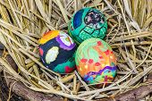 stock photo of dry grass  - Easter Eggs With Bright Drawing In A Nest From A Dry Grass - JPG