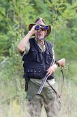 pic of shotgun  - Senior hunter with shotgun looking through binoculars in forest - JPG