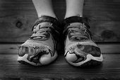 pic of human toe  - Black and white photo of shoes with holes in them and toes sticking out child kid young - JPG
