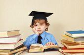 foto of professor  - Little tired professor in academic hat studies an old books - JPG