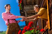pic of adultery  - Couple in love at mountain hut window wearing traditional clothing - JPG