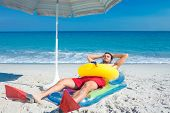 stock photo of flipper  - Man lying on the beach with flippers and rubber ring on a sunny day - JPG