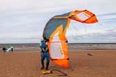 picture of kites  - Kite surfer wearing a wetsuit is preparing his kite on a windy cold day - JPG