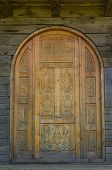 stock photo of carving  - Old carved door on wooden wall sample - JPG