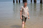 stock photo of barefoot  - Charming man barefoot at the beach on holidays - JPG