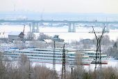 foto of passenger ship  - Passenger ships in frozen river in winter day on background of bridge - JPG