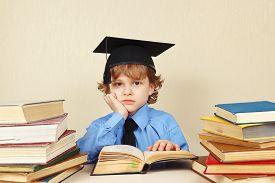 pic of professor  - Little tired professor in academic hat studies an old books - JPG