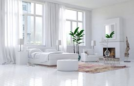 stock photo of monochromatic  - Contemporary spacious white bedroom interior with monochromatic decor and comfortable bed and armchairs below large bright sunny view windows - JPG