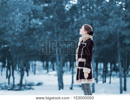 Silhouette Woman Standing Profile And Looks Up Wearing A Brown Coat In Winter Cold Snowy Scandinavia