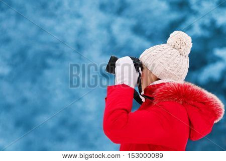 Young Woman Photographer Takes Picture On The Digital Camera Outdoors In Winter Cold Day Over Blurre