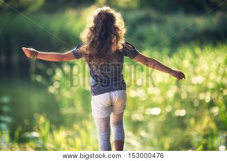 Happy little girl enjoying the nature and the sunny day in the park