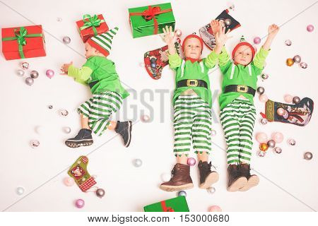 Merry Christmas 2016. Black Friday 2016. Image Cute little kids lying dressed in elf costumes. Decorated Cristmas background. Concept of celebrating holiday. Children happy to receive many gift boxes
