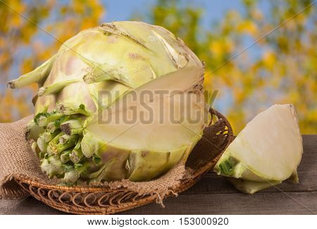 fresh cabbage kohlrabi in a wicker bowl on a dark wooden table with a blurred background.