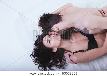 Beautiful cute loving couple is posing in a bed on a white background