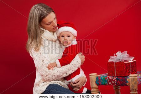 Happy young mother with her sweet baby Baby in a Christmas costume red