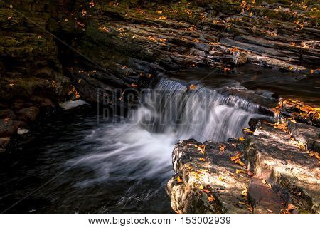 Water flows gently over rocks adorned with Autumn leaves at Raymondskill Falls near Milford, PA